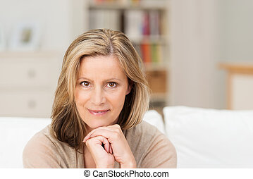 Beautiful friendly middle-aged woman sitting looking...