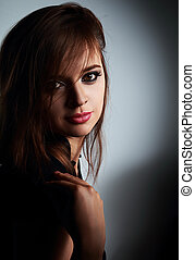 Beautiful friendly smiling young woman portrait on dark background