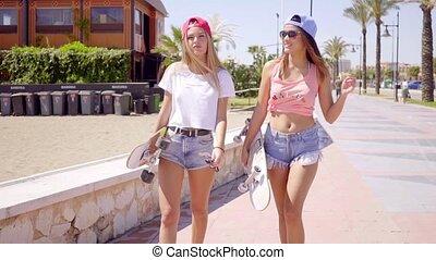 Beautiful friends walking near stone wall talk