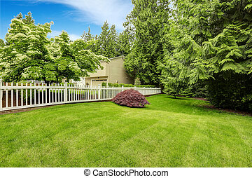 Beautiful front yard landscape with white fence