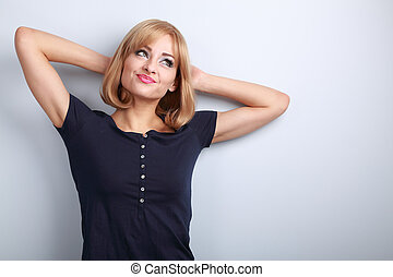 Beautiful fun thinking blond young woman in looking up on blue background