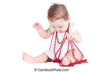 Beautiful funny baby girl playing with a red necklace, isolated