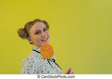 Beautiful funny girl with bright makeup holding an orange lollipop.