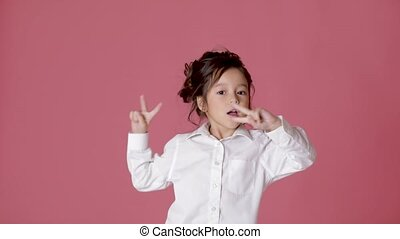 little child girl in white shirt dancing on pink background....