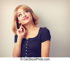Beautiful funny thinking grimacing young woman looking up. Toned closeup portrait