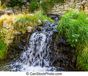 beautiful garden architecture, small waterfall streaming over rocks, nature background
