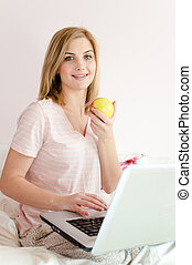 beautiful gentle sweet young woman blue eyes blond girl in bed with laptop PC computer eating apple and looking up on light copy space background closeup portrait picture