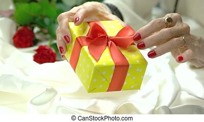 Beautiful gift box in manicured hands. Aged woman hands with...