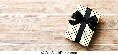 Beautiful gift box with a black bow on the yellow wooden table. Top view banner with copy space for you design