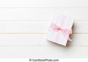 Beautiful gift box with a colored bow on the white wooden table. Top view banner with copy space for you design