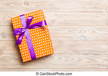Beautiful gift box with a colored bow on the yellow wooden table. Top view banner with copy space for you design