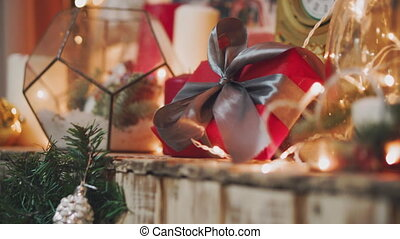 Beautiful gift in the hands of men. New Year's gift with a red ribbon, fir on the table. The man made it himself and is going to give for the holiday. Beautiful background with fireplace.