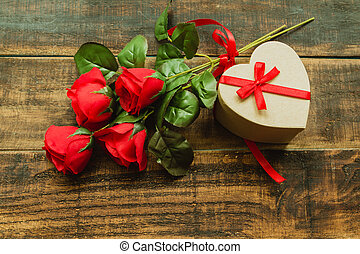 Beautiful gift with heart shape with a bouquet of red roses