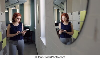 Beautiful ginger woman prints on tablet at office....