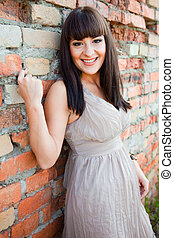 beautiful girl against old brick wall