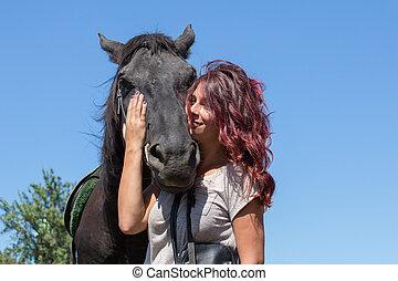 Beautiful girl and black horse in nature. Kiev, Ukraine -...
