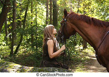 Beautiful girl and brown horse portrait in mysterious forest