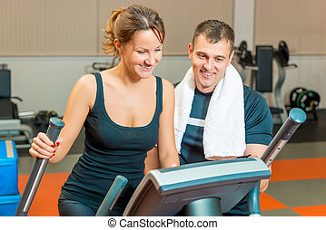 beautiful girl and personal trainer at the gym