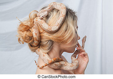 Beautiful girl and the snake Boa constrictors, which wraps...