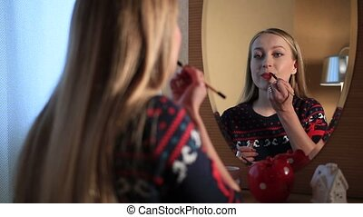 Beautiful girl applying lipstick with paint-brush