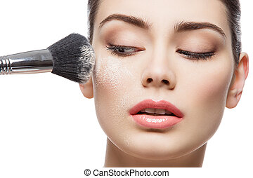 Beautiful girl applying loose powder with brush