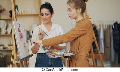 Beautiful girl art student is talking to her teacher looking...