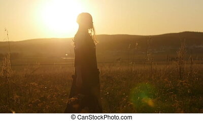 Beautiful girl at sunset in rays of sun