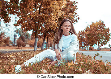 Beautiful girl, autumn day, summer in city park. Sits and rests weekend. Emotions of tenderness comfort pleasure in nature. Warm casual wear. Background of brown leaves and trees.