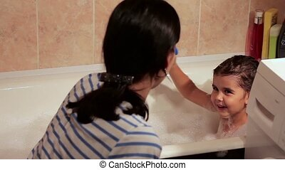 Beautiful girl bathing in a bath with foam. She laughs, has fun with her mother. play toys
