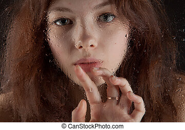 beautiful girl behind wet window