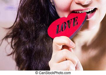 Beautiful girl biting red heart
