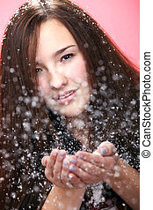 Beautiful girl blowing on christmas snow