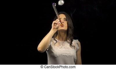 Beautiful girl blowing smoke soap bubbles