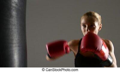 Beautiful girl boxer working with a punching bag. Gray studio