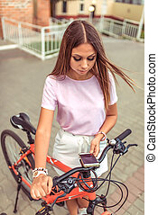 Beautiful girl brunette woman standing in the park near bike. In the summer in the city, in the hand of a smartphone, the application unlocks the parking of a bicycle.