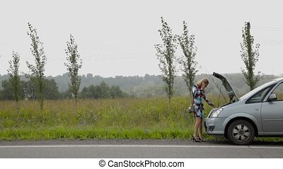 Beautiful girl calling cellphone near her broken car on a...