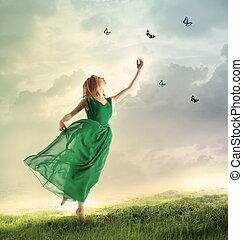 Beautiful girl catching butterflies on a mountain -...