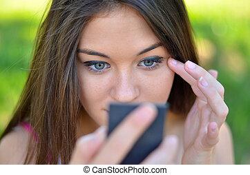 Beautiful girl checking her makeup outdoor