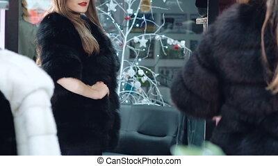 Beautiful girl chooses a fur coat in the shop
