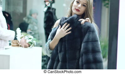 Beautiful girl chooses a fur coat in the shop