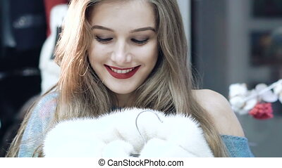 Beautiful girl chooses a fur coat in the shop Slowly