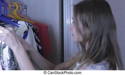 Beautiful girl chooses dress in her wardrobe. - Beautiful...