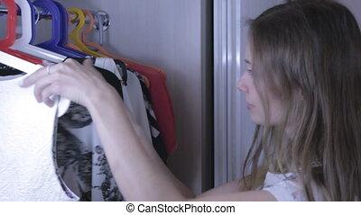 Beautiful girl chooses dress in her wardrobe.