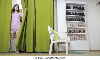 beautiful girl chooses shoes in a store