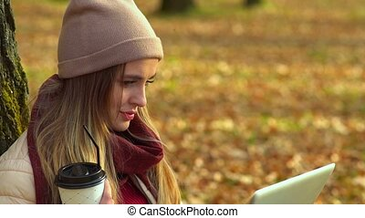 Beautiful girl, close-up, looking at the laptop screen. In autumn Park with coffee.