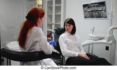 Beautiful girl consulted a dentist in his office ball on the thymus of the pain pointing to her teeth. White, sterile doctor's office. The screen shows an x-ray of the tooth in the oral cavity