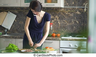 Beautiful girl cook pizza while talking on the mobile phone and smiling in kitchen at home