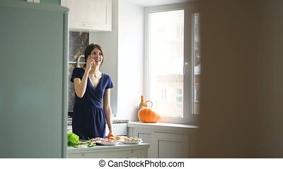 Beautiful girl cook while talking on the mobile phone and smiling in kitchen at home