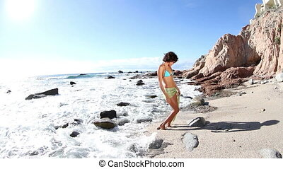 beautiful girl dances on the beach in a bikini at sunrise, cabo san lucas, mexico
