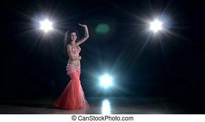 Beautiful girl dancing belly dance, on black, back light